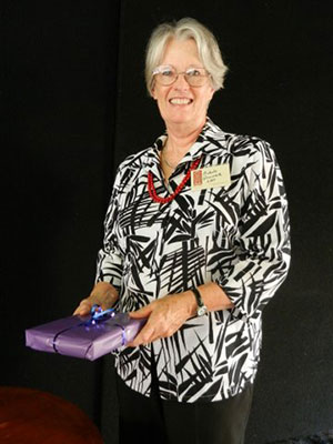 Michele Ginswick, vice-chair, holding a purple wrapped gift at the lunch hour talk